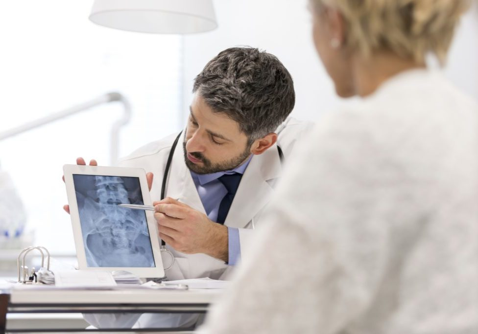 Doctor explaining x-ray on digital tablet to patient at desk in hospital